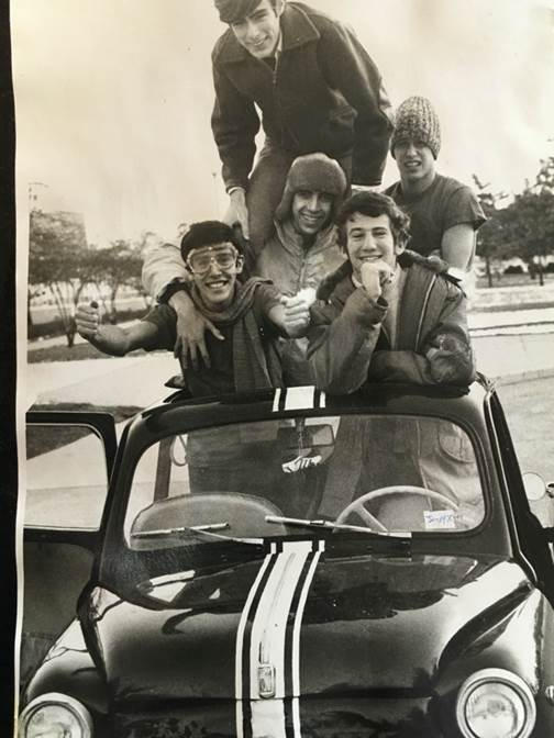 A group of people posing for a photo in front of a car  Description automatically generated